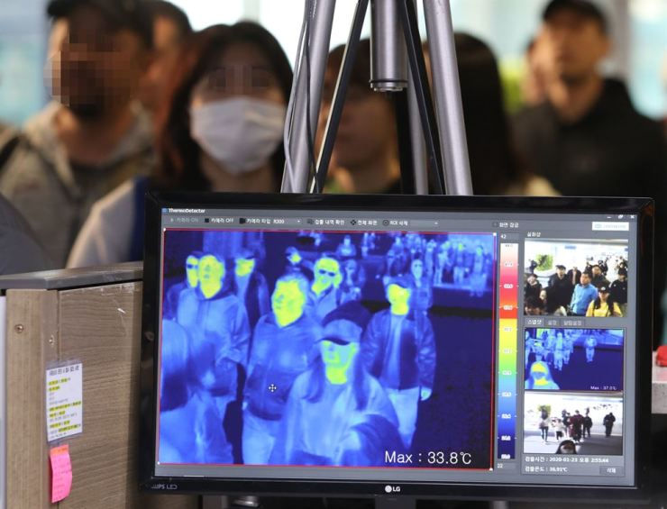 The Korean disease control and prevention force inspects arriving passengers at the Incheon International Airport, Jan. 23, for those possibly infected with the pneumonia-like illness spreading throughout China. Yonhap