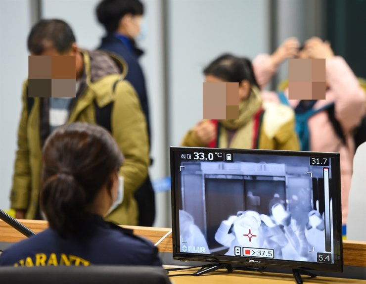 A quarantine officer checks the temperatures of passengers arriving at Pyeongtaek Port in Gyeonggi Province, Thursday, through a thermal infrared monitor. The Korea Center for Disease Control and Prevention?said it has confirmed the first suspected case of pneumonia from China. /Yonhap