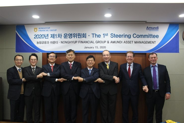 Officials from NongHyup Financial Group and Paris-based Amundi Asset Management shake hands during this year's first steering committee meeting at the group's headquarters in Seoul, Jan. 15. At the meeting, they agreed to cooperate to strengthen NH-Amundi Asset Management's overseas investment. Amundi is NH-Amundi's second largest shareholder. Courtesy of NongHyup Financial Group