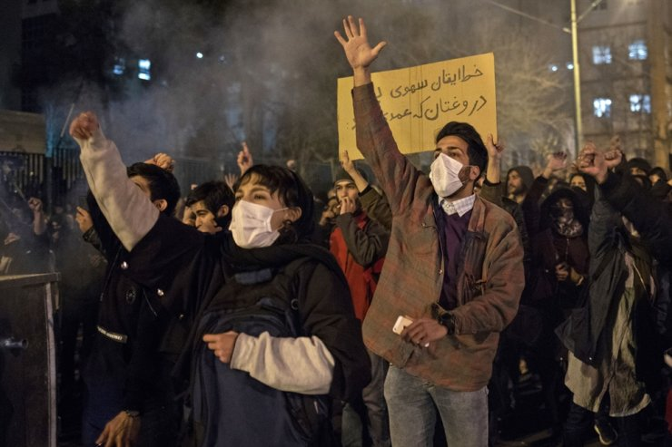 Iranians chant slogans and hold a placard reading in Farsi 'Your mistake was unintentional, your lie was intentional' during a demonstration outside Tehran's Amir Kabir University on Jan. 11, 2020. AFP