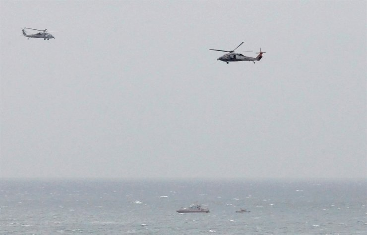 A Iranian Revolutionary Guard boat is seen near a U.S. aircraft carrier in the Strait of Hormuz as U.S. Navy helicopters hover over it, March 21, 2017. Reuters