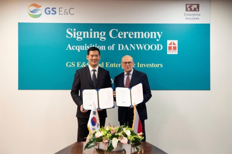 Huh Yoon-hong, president of New Business of GS E&C takes picture with Jacek Siwicki, the president of Enterprise Investors, after the signing ceremony for the acquisition of Danwood held at Danwood headquarters in Poland, Monday, local time./ Courtesy of GS Engineering & Construction.