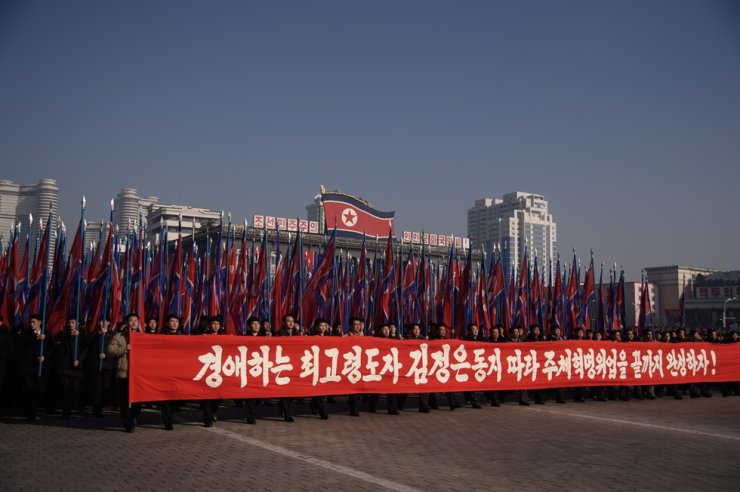 People hold a banner reading 'Let us complete the revolutionary cause of Juche following the leadership of the respected Supreme Leader Kim Jong-un' as they attend a rally in support of the 5th Plenary Meeting of the 7th Central Committee of the Workers' Party of Korea at Kim Il Sung Square in Pyongyang on Jan. 5, 2020. AFP