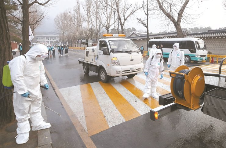 Officials from the Jongno District Office disinfect streets near Cheong Wa Dae in downtown Seoul, Thursday, to prevent the spread of COVID-19 the new coronavirus that originated in Wuhan, China. They began the operation after removing protest tents set up by the Korean Teachers and Education Workers Union and other civic groups. / Yonhap