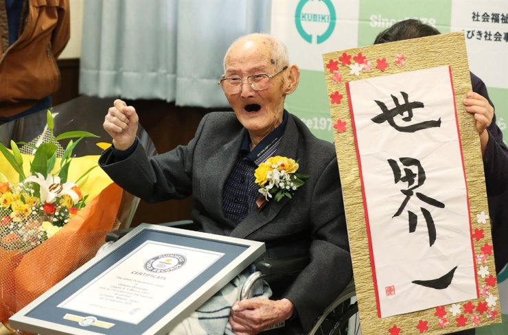 In this handout picture taken and released by Guineess World Records LTD. via Jiji Press on Feb. 12, 2020, Japanese Chitetsu Watanabe, aged 112, poses next to the calligraphy reading in Japanese 'World Number One' after he was awarded as the world's oldest living male in Joetsu, Niigata prefecture. AFP