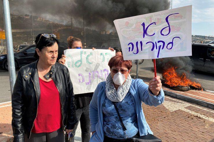 Residents hold placards as they demonstrate against a report that Israel may quarantine visitors from Korea at a military base in the Jewish settlement of Har Gilo in the Israeli-occupied West Bank Februar, Sunday. / Reuters-Yonhap