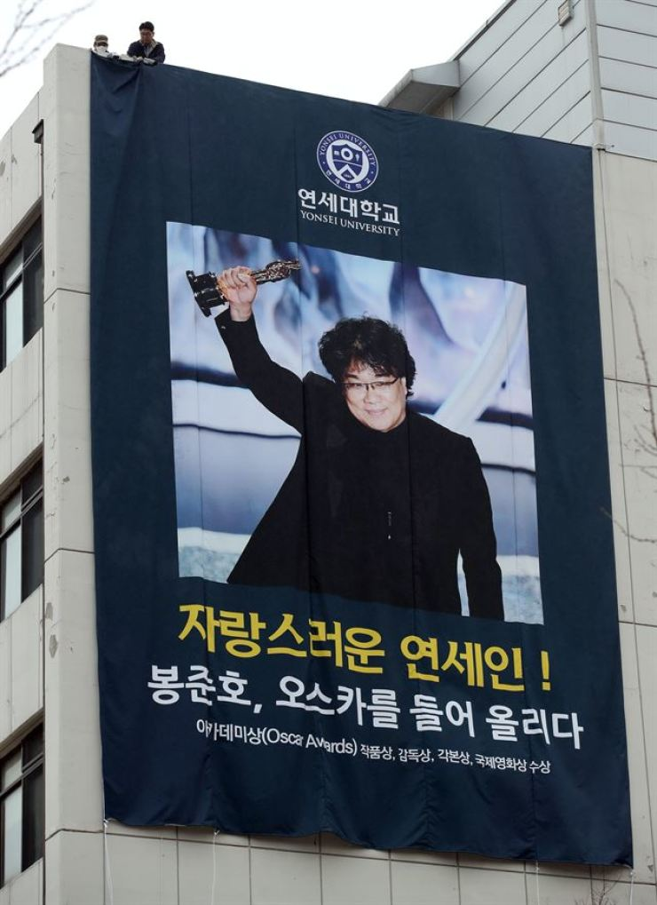 A big banner bearing the photo of director Bong Joon-ho raising his Oscar trophy drapes a wall of a building in Yonsei University, his alma mater. Yonhap
