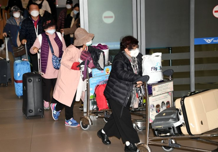 Korean tourists leave Incheon International Airport, Tuesday, after returning home on an Israeli charter flight following the Israeli government's entry ban on Koreans out of concerns over the coronavirus. / Yonhap
