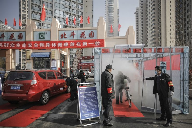 Security guards hold the curtain for a cyclist to past through a disinfectant spray in order to return home at a residential complex in northern China's Tianjin Municipality Tuesday, Feb. 11, 2020. AP