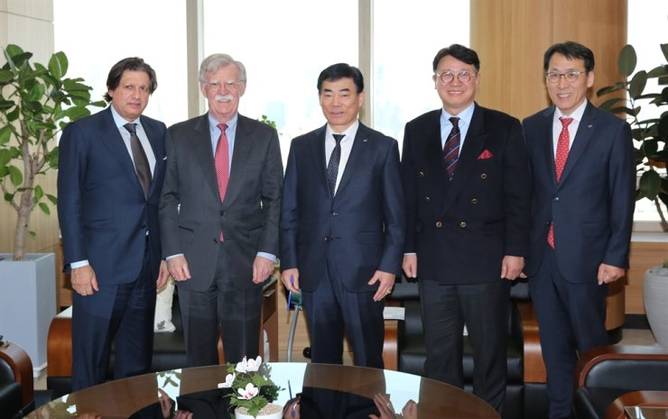 Rhone Group co-founder Robert Agostinelli, left, and senior adviser John Bolton, second from left, pose with Military Mutual Aid Association (MMAA) CEO Kim Do-ho, center, and other MMAA executives at the association's headquarters in Seoul, Monday. / Courtesy of MMAA