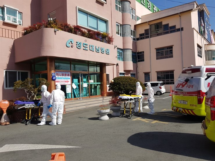 Heath officials in protective gear stand outside Daenam Hospital in Cheongdo, North Gyeongsang Province, Monday. Yonhap