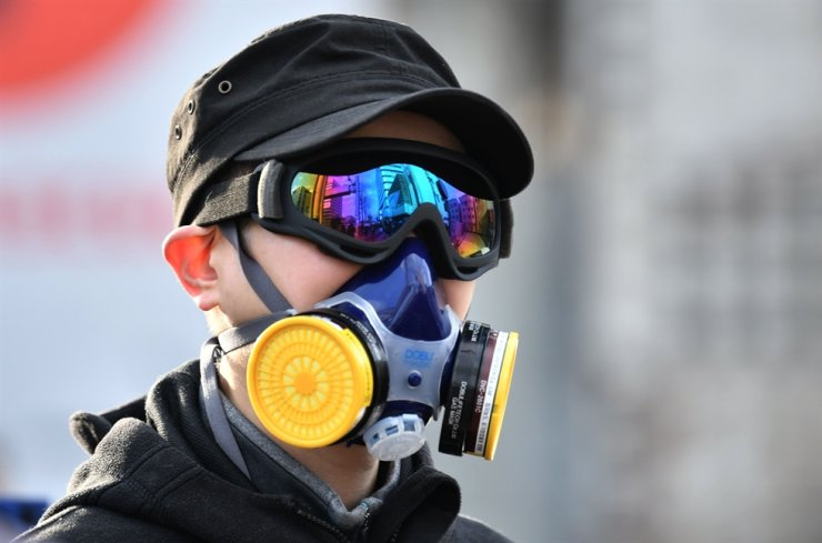 A man wears a mask and goggles as he waits in line to buy face masks from a post office near the Daegu branch of Shincheonji on Feb. 27, 2020. The secretive religious group at the center of Korea's coronavirus outbreak is a sprawling network so wealthy it can mobilize thousands of believers to hold Pyongyang-style mass performances at Seoul's Olympic stadium. AFP