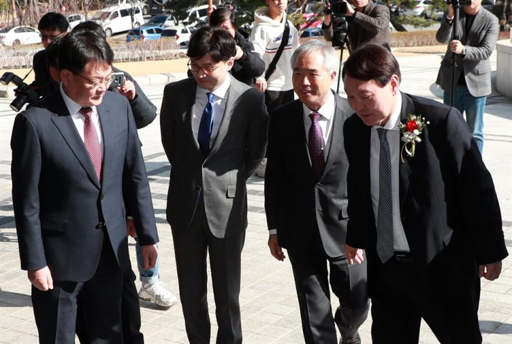 Yoon Seok-youl, right, prosecutor general greets his colleagues as he arrives at the Busan High Prosecutors' Office in Busan, Thursday./ Yonhap