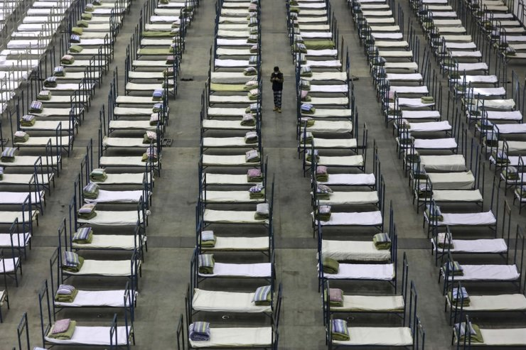 In this Feb. 4, file photo, a worker walks among beds in a convention center that has been converted into a temporary hospital in Wuhan in central China's Hubei Province. AP-Yonhap