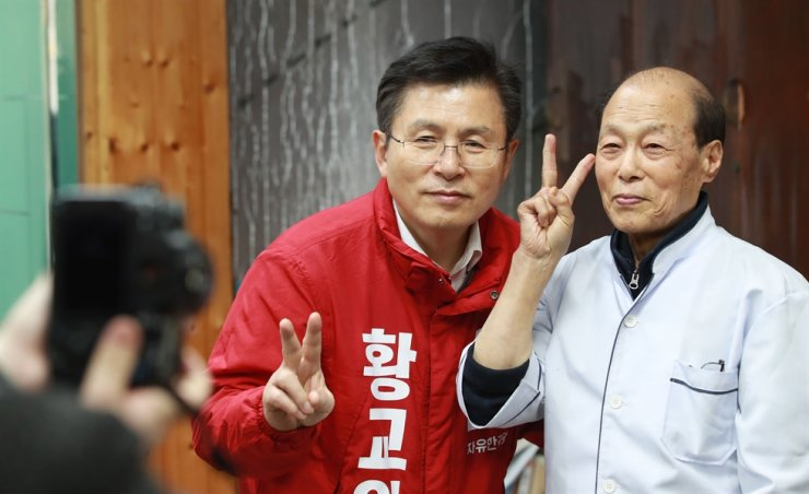 Main opposition Liberty Korea Party Chairman Hwang Kyo-ahn, left, poses with a barber during his visit to Jongno District, Sunday, where he will be running as an April 15 general election candidate. Yonhap
