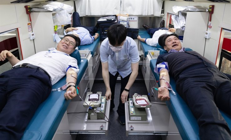 Korea Investment & Securities CEO Jung Il-mun, left, donates blood alongside the company's union head Park Jong-bae in a Korea Red Cross blood donation bus located in front of the brokerage's headquarters on Yeouido, Thursday. The company's two-day blood donation campaign aims to help hospitals that have a shortage due to the coronavirus outbreak. / Courtesy of Korea Investment & Securities
