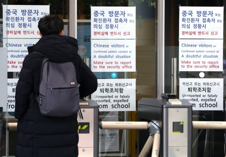 A student reads warning signs about the new coronavirus at University of Seoul in Seoul, Feb. 4. Korea Times file