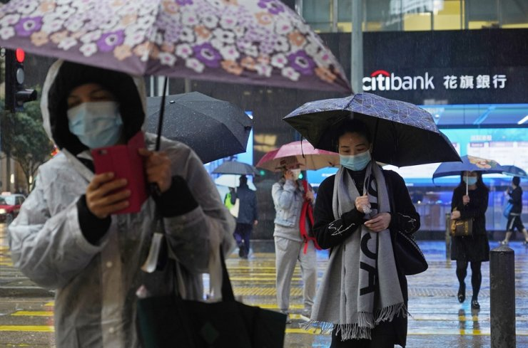People wear protective face masks on a street corner in rain in Hong Kong, Thursday, Feb. 13, 2020. AP