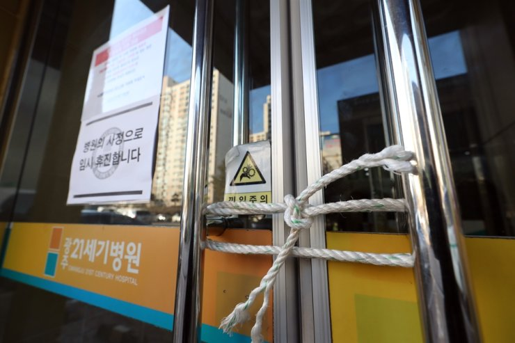 An entrance door of Gwangju 21st Century Hospital in Gwangju, where the country's 16th novel coronavirus infection patient was cohort-quarantined, is tied with a rope on Wednesday. Yonhap