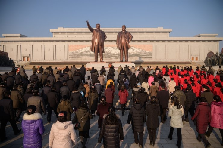 In a photo taken on Feb. 8, 2020, people bow before the statues of late North Korean leaders Kim Il-sung and Kim Jong-il on Mansu Hill, to mark the 72nd anniversary of the founding of Korean People's Army in Pyongyang. AFP