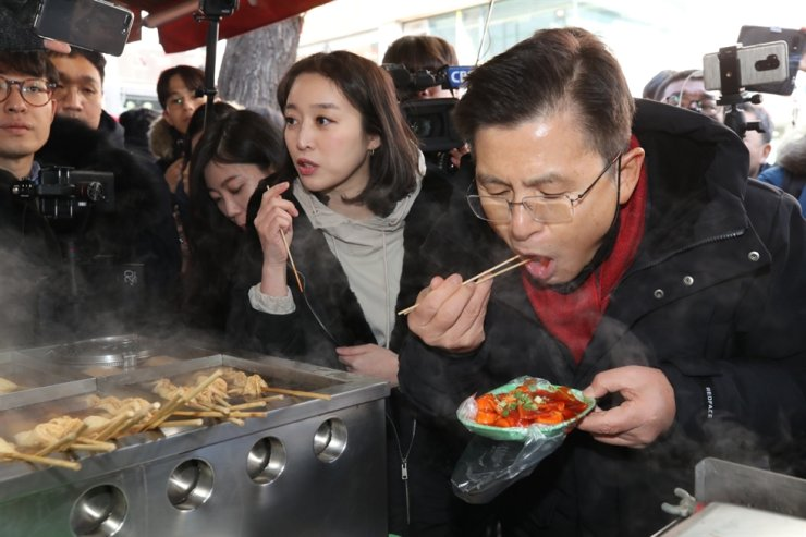 Main opposition Liberty Korea Party Chairman Hwang Kyo-ahn eats tteokbokki at a snack bar near Sungkyunkwan University in central Seoul, Sunday, during his election campaign. Yonhap