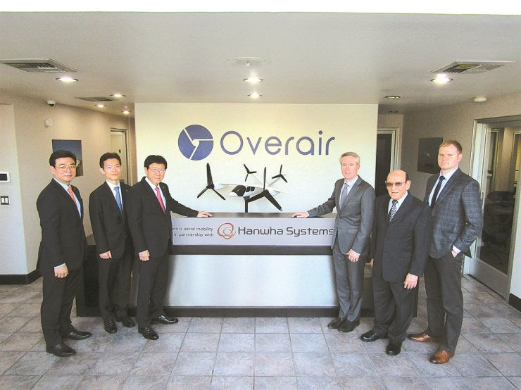 Hanwha Systems CEO Kim Youn-chul, third from left, poses with Overair CEO Ben Tigner, fourth from left, and other company executives during a ceremony at the Overair headquarters in Los Angeles, Friday, to mark their joint development of air taxis. On Dec. 8, the two firms inked a $25 million deal to build personalized aerial vehicles. Courtesy of Hanwha Systems