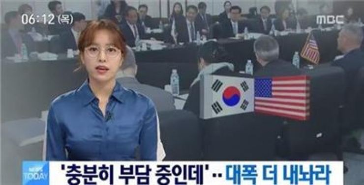 Lim Hyun-ju, news presenter of local broadcaster MBC, appears wearing glasses on a news program in this April. 12, 2018 file photo. Her decision to wear glasses sparked debate online. Korea Times file