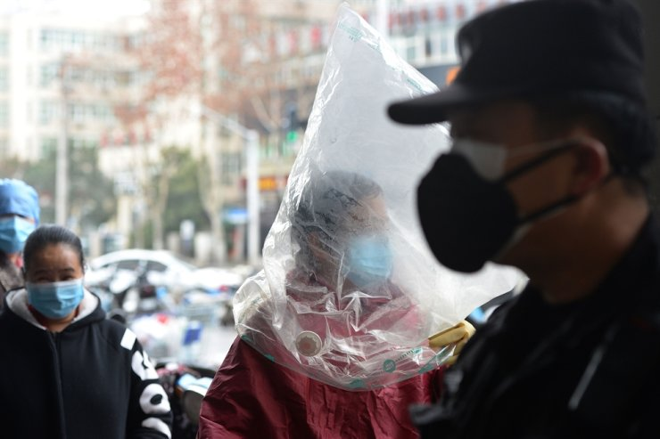 A resident wearing a protective mask and a plastic bag is seen outside a supermarket in Wuhan, the epicenter of the outbreak of the novel coronavirus, in China's central Hubei Province. AFP