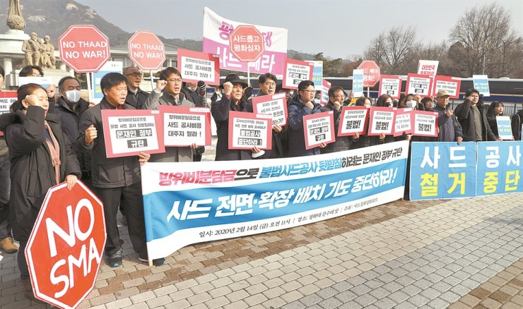 Members of a civic group hold a press conference in front of Cheong Wa Dae in Seoul, Friday, to protest against the alleged U.S. plan to push Korea to fund a Terminal High Altitude Area Defense (THAAD) base in Seongju, North Gyeongsang Province. They demanded that the U.S. and Korea remove the anti-missile system from Korea. / Yonhap