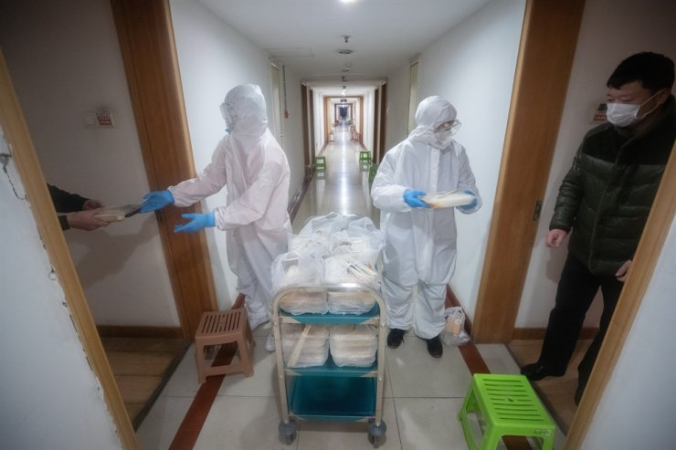 Staff in protective clothing distribute food to patients that were quarantined in a hotel in Wuhan City, Hubei Province, Feb. 5. EPA