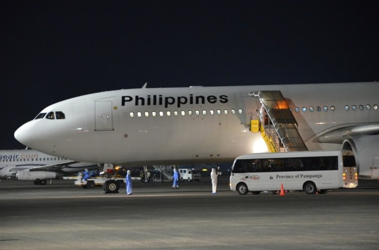 In this handout photo released by Department of Foreign Affairs, members of the DFA and Department of Health wear protective suits as they assist Filipinos from the Diamond Princess Cruise Ship as they arrive at the Clark airbase, Pampanga, northern Philippines early Wednesday, Feb. 26, 2020. AP