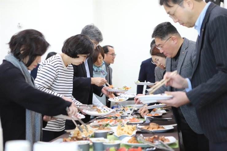 Sejong University officials participate in a food tasting event held on Feb. 5 to celebrate the school's successful salmon farming. / Courtesy of Sejong University