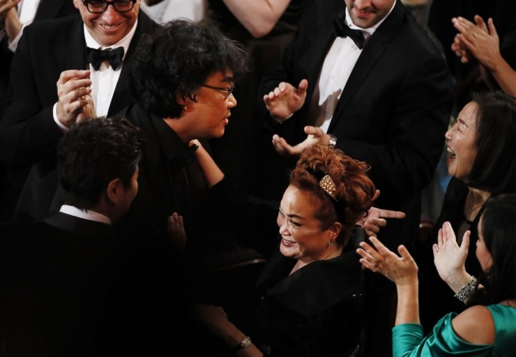 Director Bong Joon-ho reacts with CJ Group Vice Chairwoman Lee Mi-kyung and cast and crew after winning the Oscar for the Best Motion Picture for