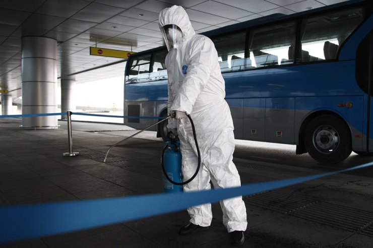 In this Feb. 1 photo, a State Commission of Quality Management staff member disinfects a ground transportation area at North Korea's Pyongyang Airport. AP