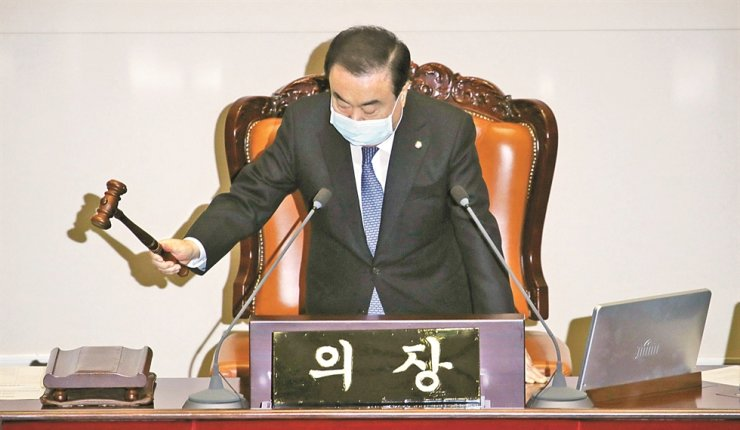 National Assembly Speaker Moon Hee-sang bangs the gavel to announce the start of a plenary session at the National Assembly, Wednesday, wearing a facial mask to protect against COVID-2019 infection. The Assembly reopened earlier in the day after a 24-hour temporary shutdown to allow for disinfection operations. Yonhap