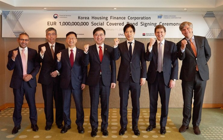 Korea Housing Finance Corp. (HF) CEO Lee Jung-hwan, third from left, poses with Financial Services Commission Vice Chairman Sohn Byung-doo, center, Busan Vice Mayor Park Sung-hoon, third from right, and foreign financial firm officials at the Westin Chosun Busan, Tuesday. They celebrated the issuance of Asia's first negative yielding social covered bond denominated in euro, which is considered to show global investors' trust in the state-run financial company. / Courtesy of HF