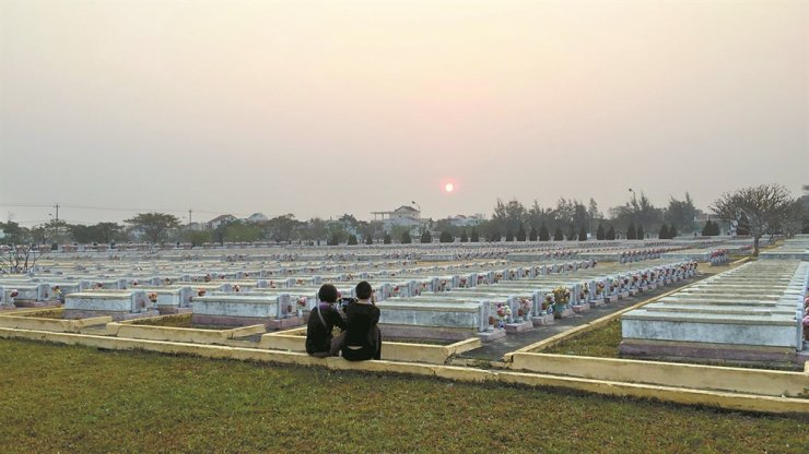 Director Lee-Kil Bora, right, stares at the graves in the military cemetery in Hoi An, Vietnam, in this March 8, 2016 photo. / Courtesy of Cinema Dal