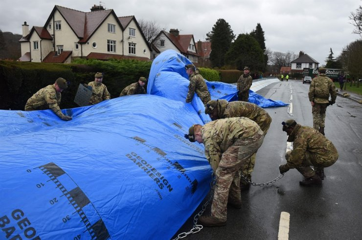Members of the 4th Battalion Royal Regiment of Scotland erect flood barricades in Ilkley, West Yorkshire on February 15, 2020, as Storm Dennis sweeps in over the country. AFP