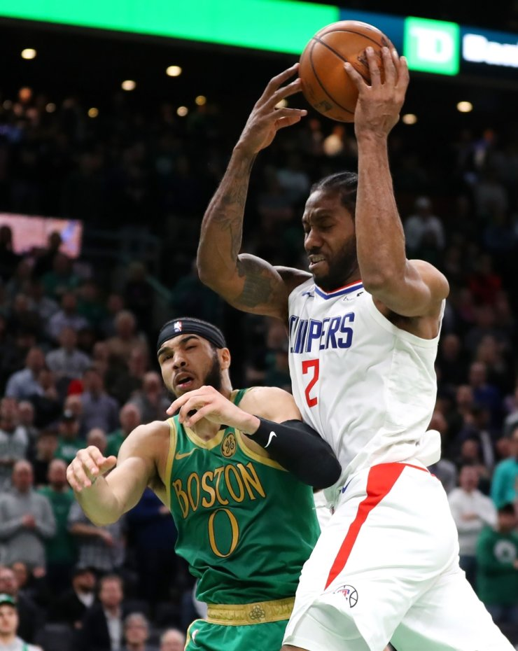 Kawhi Leonard, right, of the LA Clippers grabs a rebound over Jayson Tatum of the Boston Celtics at TD Garden on Thursday in Boston, Massachusetts. The Celtics defeat the Clippers in double overtime 141-133. / AFP-Yonhap