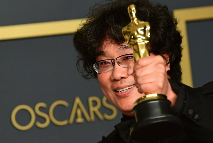 Parasite director Bong Joon-ho holds up one of the four Oscars his film won at the Academy Awards in Los Angeles, Feb. 9 / AFP-Yonhap