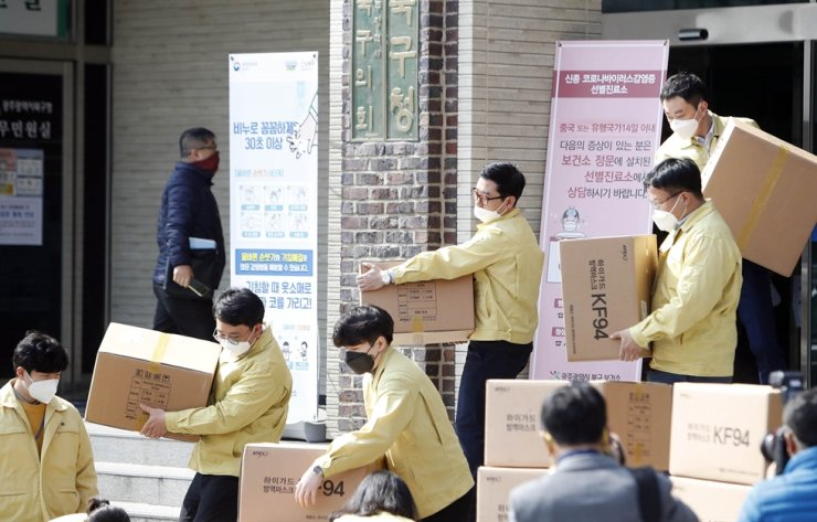 Civil servants working at Gwangju's Buk-gu office organize boxes that contain face masks, Thursday. The boxes will be delivered to Daegu where coronavirus infection cases are on the rise, Thursday. / Yonhap