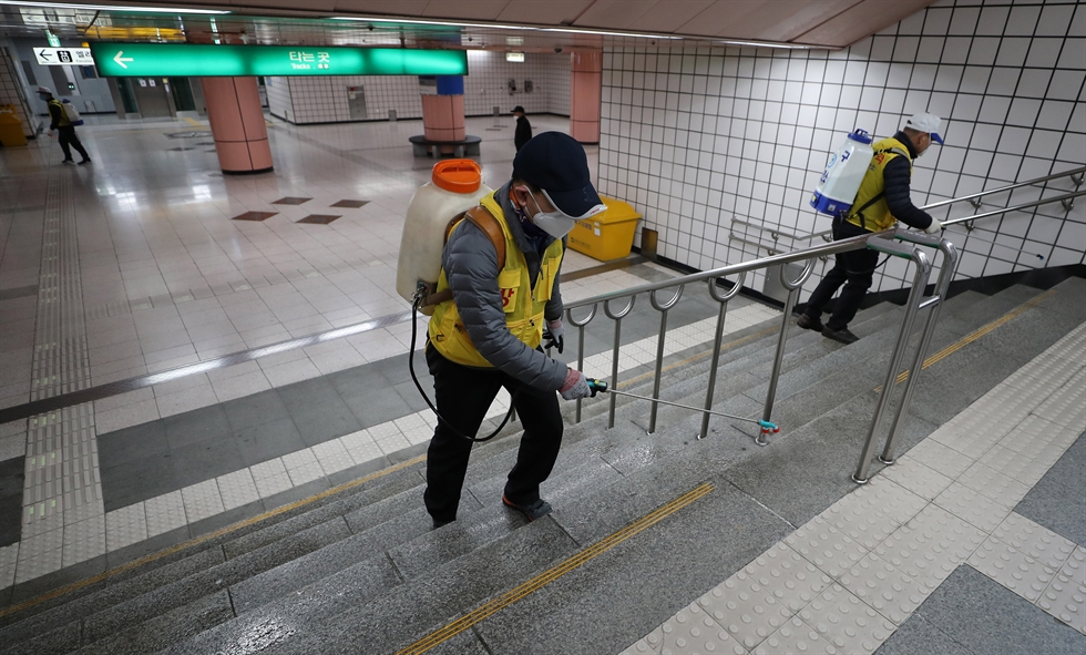 A health officer disinfects the entrance of a multi-unit house in Daegu where one of its residents tested positive for the coronavirus, Thursday. Yonhap