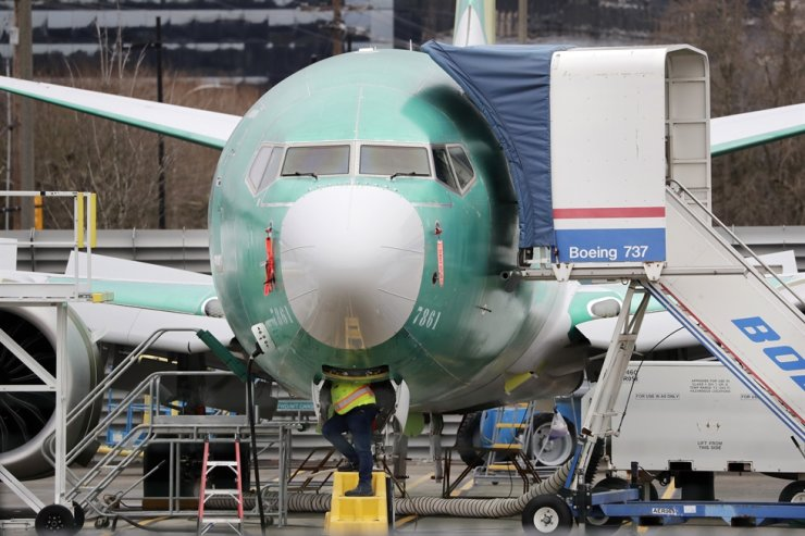In this Dec. 16, 2019, file photo, a worker looks up underneath a Boeing 737 MAX jet in Renton, Wash. Boeing sold no new airline jets in January, and now the company is worried that the virus outbreak in China could hurt airplane deliveries in the first quarter. AP
