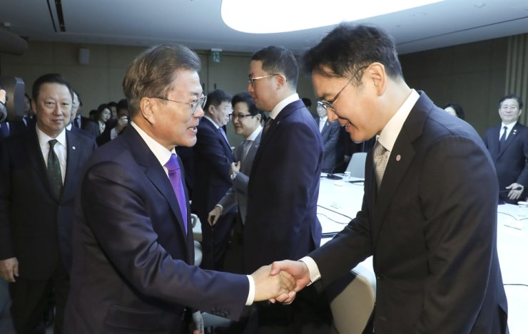 President Moon Jae-in, left, shakes hands with Samsung Electronics Vice Chairman Lee Jae-yong before the start of a meeting with leaders of the country's leading businesses at the Korea Chamber of Commerce and Industry (KCCI) headquarters, downtown Seoul, Thursday. Yonhap