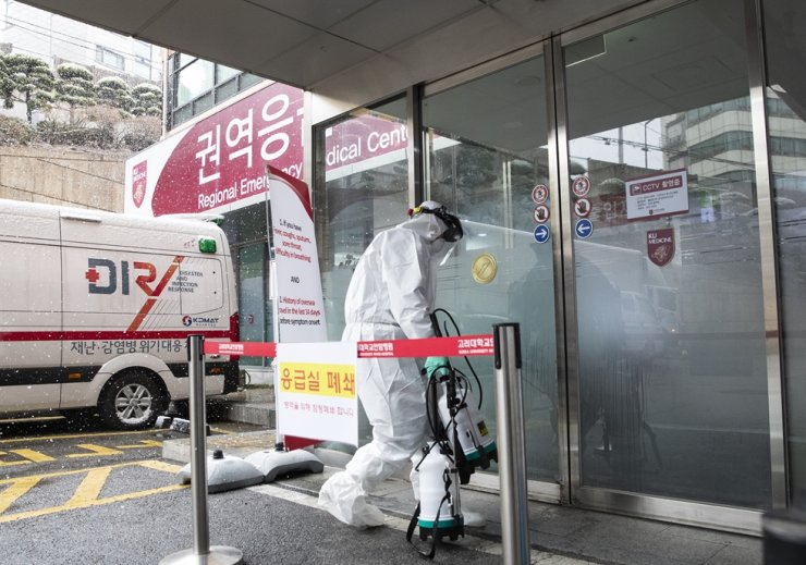 A staff member carries out disinfection at the Korea University Anam Hospital Regional Emergency Medical Center in Seoul, Sunday, after the 29th coronavirus patient visited there and tested positive. /Yonhap