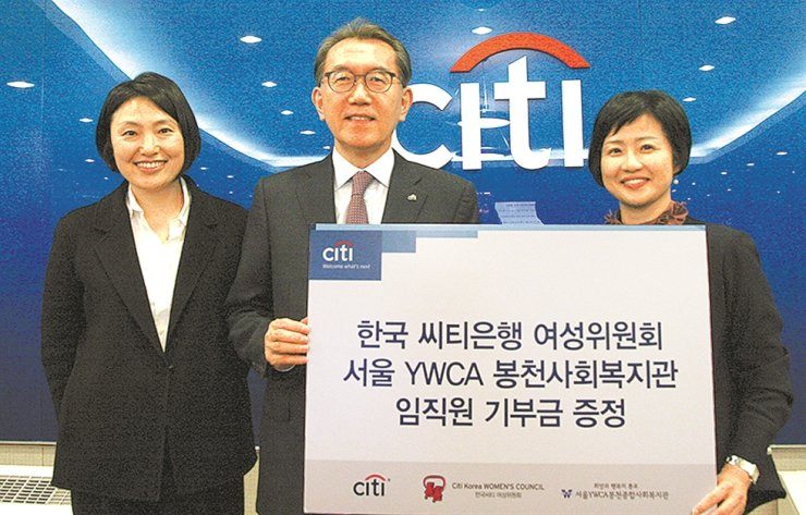 Citibank Korea CEO Park Jin-hei, center, poses with Seoul YWCA chief Lee Yoo-rim, right, after donating funds raised from a campaign to support single-parent families, at the bank's headquarters in central Seoul, Thursday. The lender plans to hold the campaign every year. / Courtesy of Citibank