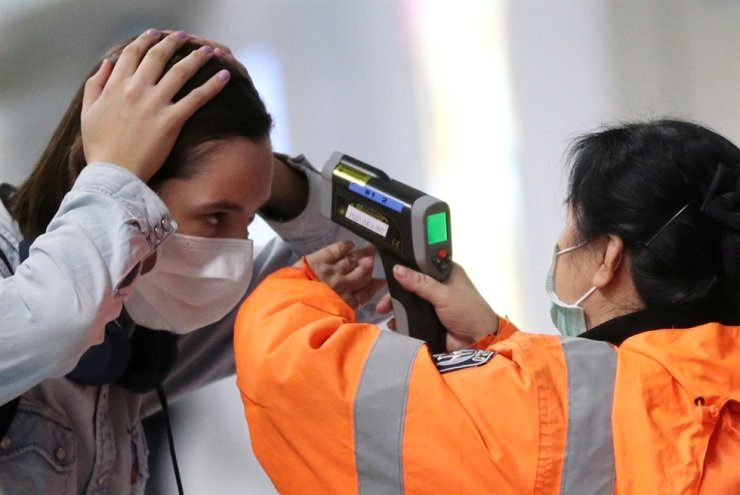 A worker checks the temperature of a passenger arriving into Hong Kong International Airport with an infrared thermometer, following the coronavirus outbreak in Hong Kong, China, Feb. 7, 2020. Reuters-Yonhap