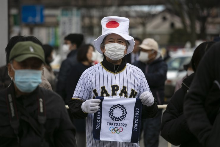 A man wearing a Japanese flag-themed hat shows a towel with a Tokyo 2020 Olympics logo printed on while waiting in line to view the Olympic Flame in Fukushima City, Japan, Tuesday. / AP-Yonhap