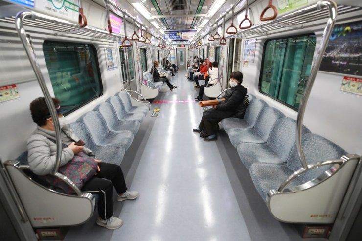 Passengers on a subway train in the Southeastern city of Daegu sit apart, Monday, after the government enforced two weeks of social distancing nationwide to prevent the spread of COVID-19. /Yonhap