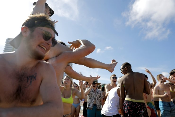 Spring break revelers party together Tuesday, March 17, 2020, in Pompano Beach, Fla. As a response to the coronavirus pandemic, Florida Gov. Ron DeSantis ordered all bars be shut down for 30 days beginning at 5 p.m. and many Florida beaches are turning away spring break crowds urging them to engage in social distancing. (AP Photo/Julio Cortez)